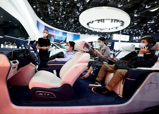 베이징모터쇼에 참석한 관람객들이 안내원의 설명을 듣고 있다. 코로나19를 의식해 모두 마스크를 착용했다. [GettyImage]