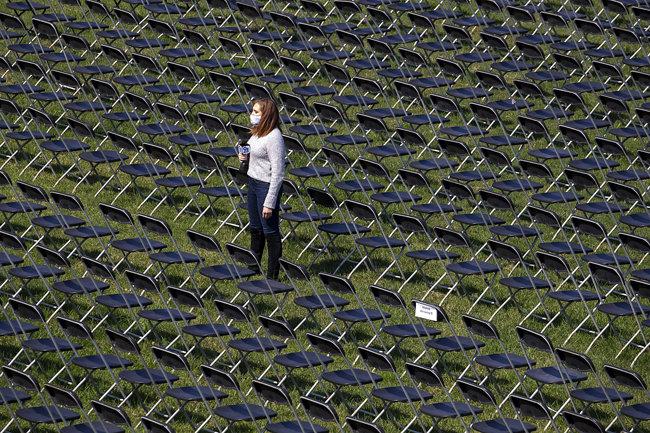 10월 4일(현지 시간) 미국 백악관 근처 일립스 공원에 놓인 2만 개의 빈 의자 사이에 한 취재기자가 서 있다. [GettyImage]