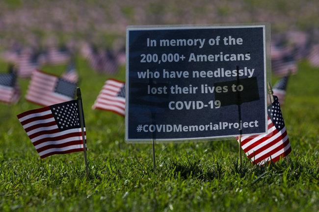 워싱턴 내셔널 몰 잔디광장의 성조기 옆에 '20만 명이 넘는 미국 코로나19 사망자를 기억한다'는 내용의 글이 적혀 있다. [GettyImage]