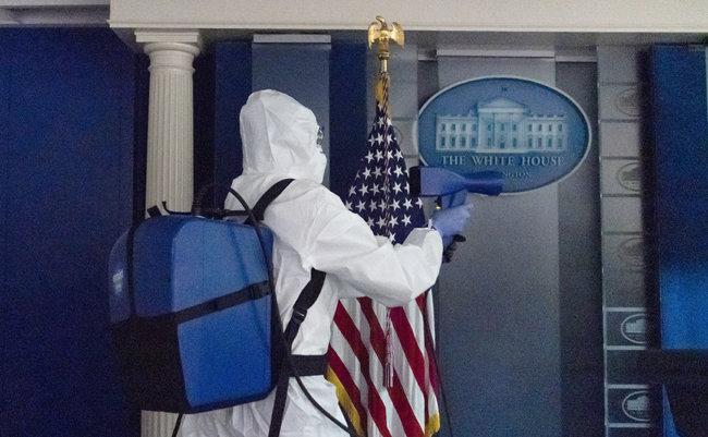 도널드 트럼프 미국 대통령이 퇴원한 10월 5일(현지 시간) 보호복을 착용한 방역 인력이 백악관 기자실에 소독약을 뿌리고 있다. [워싱턴=AP 뉴시스]