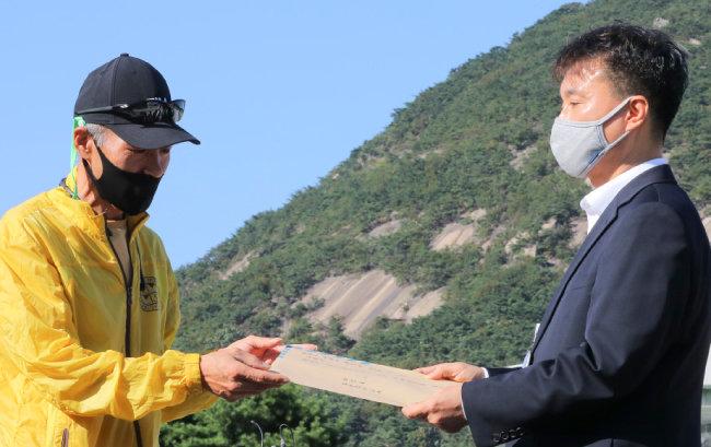 북한에 살해된 공무원 이모 씨 친형 이래진 씨(왼쪽)가 10월 8일 청와대 앞에서 피살 공무원 이씨의 아들이 문재인 대통령에게 쓴 편지를 전달했다. [원대연 동아일보 기자]