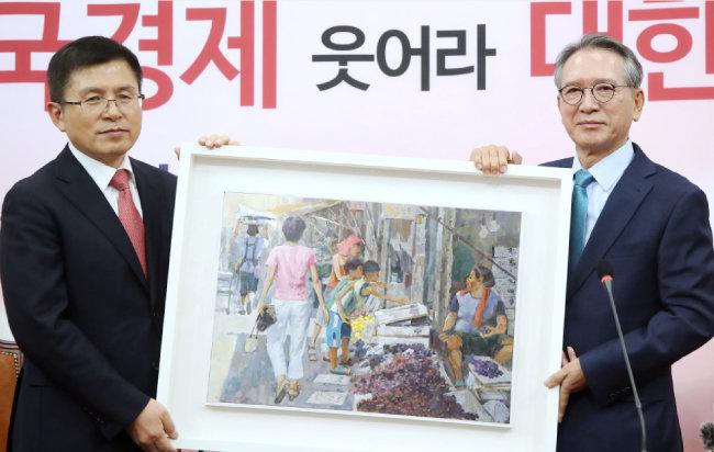 황교안 자유한국당 당시 대표가 1월 17일 서울 여의도 국회에서 한국당 공천관리위원장으로 임명된 김형오 전 의장과 회동, 그림을 선물받고 있다.  [뉴시스]