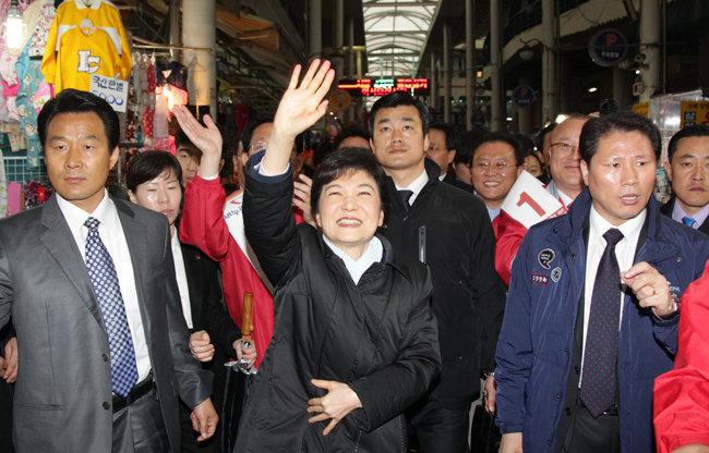 2012년 3월 23일 대구 서문시장을 방문한 박근혜 당시 새누리당 비상대책위원장(가운데)이 시민들에게 손을 흔들며 인사하고 있다. [동아DB]