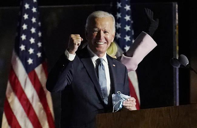 """11월 4일(현지시간) 조 바이든 미국 민주당 대선 후보가 델라웨어주 윌밍턴의 한 행사장에서 연설 전 마스크를 벗으며 미소 짓고 있다. 이날 그는 """"우리가 승자가 되어 있을 것으로 확실히 믿는다""""고 말했다. [AP=뉴시스]"""