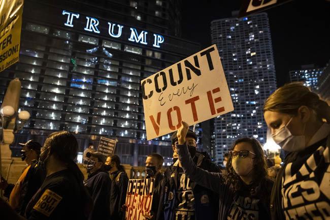 11월 4일(현지 시간) 미국 시카고에서 반(反)트럼프 성향 시민들이 '모든 표를 집계하라'는 문구가 적힌 팻말을 든 채 시위를 벌였다. 이들 뒤로 '트럼프 인터내셔널 호텔' 간판이 보인다. 같은 날 트럼프 캠프는 펜실베이니아와 미시간, 조지아 등에서의 개표 중단을 요구하며 잇달아 소송을 제기했다. [AP=뉴시스]