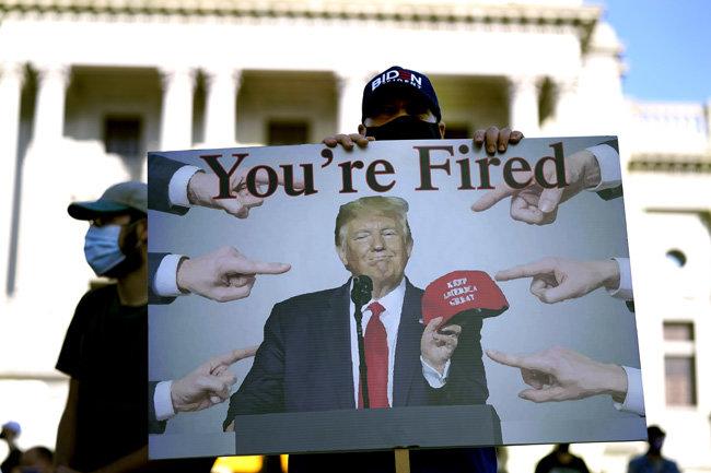 11월 7일(현지 시간) 조 바이든 미국 대통령 당선인 지지자가 펜실베이니아주 해리스버그의 주 의회의사당 인근에서 도널드 트럼프 대통령이 TV프로그램 진행자 시절 유행시킨 '넌 해고야'란 글씨가 쓰인 팻말을 들고 서 있다. [해리스버그=AP뉴시스]