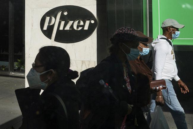 미국 제약사 화이자가 독일 기업 바이오엔테크와 공동으로 개발 중인 코로나19 백신의 예방효과가 90% 이상인 것으로 확인됐다고 발표한 11월 9일(현지 시간) 마스크를 착용한 시민들이 미국 뉴욕 화이자 본사 앞을 지나고 있다. [뉴욕=AP뉴시스]