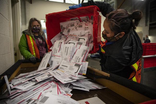 미국 대선이 치러진 11월 3일(현지시간) 오리건주 포틀랜드의 한 개표소에서 담당 인력들이 투표함에 담긴 우편투표 용지를 책상 위로 들이붓고 있다. 오리건주는 1998년 11월부터 모든 공직자 선거를 100% 우편투표로만 진행하고 있다. [포틀랜드=AP뉴시스]