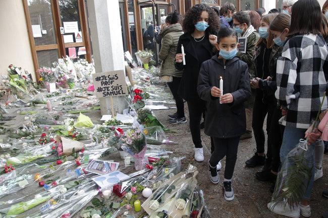 수업 중 이슬람 선지자 무함마드를 풍자한 만평을 보여줬다는 이유로 무슬림 청년에게 테러를 당한 프랑스 역사 교사 사뮈엘 파티를 추모하는 시민들이 10월 17일(현지시간) 그가 근무하던 파리 북부 콩플랑생토노린의 부아돈 중학교 앞에 꽃을 놓고 촛불을 켰다. [콩플랑생토노린=AP 뉴시스]