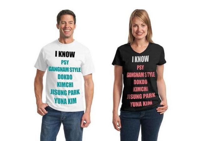 """외국인 남녀 두 명이 각각 흰색과 검은색 티셔츠를 입고 환하게 웃는 모습. 티셔츠에는 """"나는 싸이·강남스타일·독도·김치·박지성·김연아를 알고 있다""""란 문구가 쓰여 있다. [온라인 커뮤니티]"""