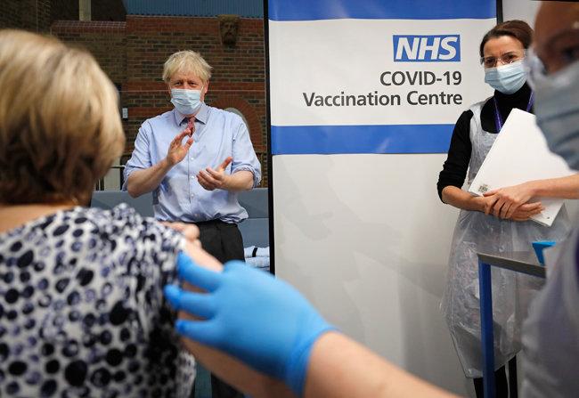 """보리스 존슨 영국 총리(왼쪽에서 두 번째)가 영국 런던 가이 병원에서 진행된 코로나19 백신 접종 모습을 지켜보고 있다. 이날 존슨 총리는 """"코로나19 백신에 대해 하나도 불안해하고 걱정할 게 없다""""고 강조했다. [GettyImages]"""