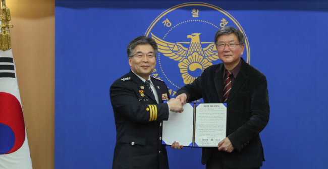 2020년 2월 25일 민갑룡 경찰청장과 홍세화(오른쪽) 장발장은행장이 서울 미근동 경찰청사에서 협약서에 서명하고 있다. [경찰청 제공]
