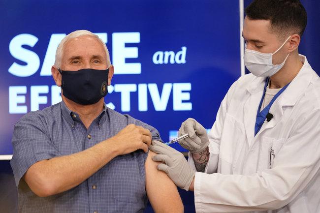 마이크 펜스 미국 부통령(왼쪽)이 12월 18일(현지 시간) 백악관 아이젠하워 행정동에서 화이자의 신종 코로나바이러스 감염증 백신을 접종 받고 있다. 이 과정은 TV 생중계됐다. [워싱턴=AP 뉴시스]