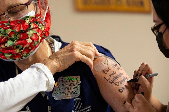 미국 워싱턴주 시애틀에 있는 원주민 대상 의료기관 '시애틀 원주민 보건위원회(SIHB)' 소속 의사 테레사 마레스카 씨가 12월 21일(현지시간) 코로나19 백신을 맞은 뒤 한 동료가 그의 팔에 이 의료기관 슬로건 'For the Love of Native People'을 쓰고 있다. [Getty Images]