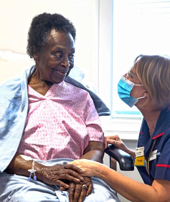 12월 8일(현지시간) 영국 런던 로열 프리 병원에서 80세 조세핀 팔레예 씨가 코로나19 백신을 맞은 뒤 간호사 손을 잡고 웃고 있다. [Getty Images]