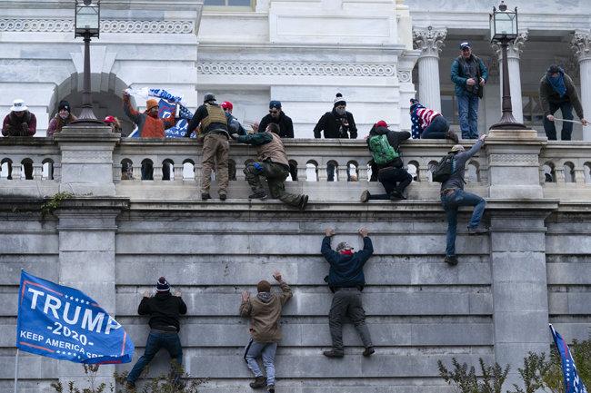도널드 트럼프 미국 대통령 열성 지지자인 '트럼피스트'들이 1월 6일(현지 시간) 워싱턴 국회의사당에 난입하려고 외벽을 기어오르고 있다. [AP 뉴시스]