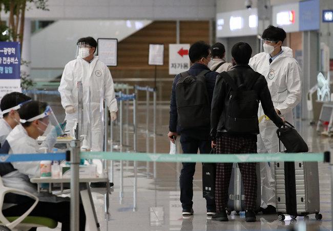 지난해 12월 31일 오후 인천국제공항 제2터미널 입국장에서 입국자가 방역 당국의 안내를 받고 있다. [뉴스1]