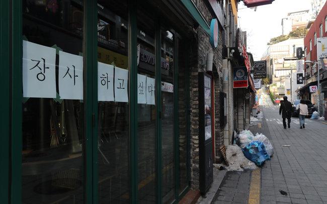 1월 14일 서울 용산구 이태원 거리에서 코로나19 타격으로 사실상 폐업절차를 밟고 있는 한 가게에 '장사하고 싶다'는 글귀가 붙어 있다. [홍진환 동아일보 기자]