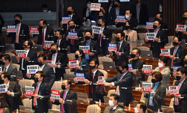 2월 10일 서울 여의도 국회 본회의장에서 고위공직자범죄수사처(공수처)법 개정안이 통과되자 국민의힘 의원들이 일제히 자리에서 일어나 '민주주의는 죽었다' 등의 손팻말을 들고 항의했다. [김동주 동아일보 기자]