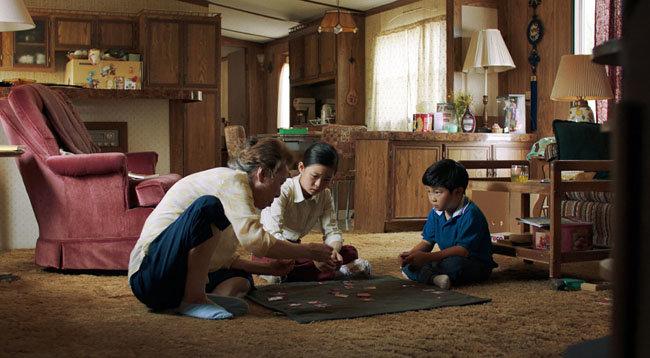 영화 '미나리'에서 윤여정(왼쪽)이 손녀 앤(노엘 조·가운데)과 손자 데이비드(앨런 김)에게 화투 치는 법을 가르쳐주는 장면. [판씨네마 제공]