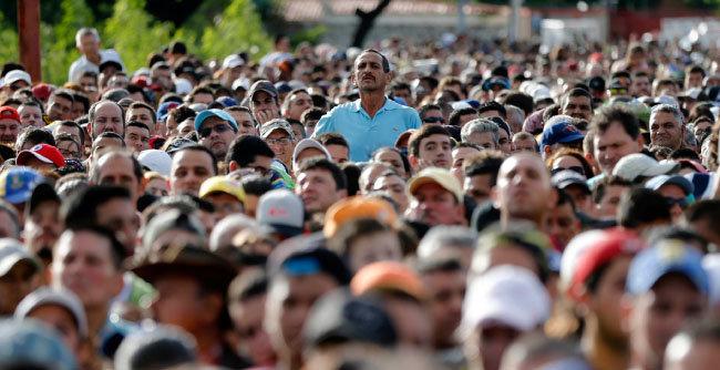 2016년 7월 17일 한 남자가 베네수엘라를 떠나 콜롬비아 국경으로 넘어가기를 기다리는 군중 위에 서 있다. 콜롬비아 당국은 2017년 12월 22일 약 55만 명의 베네수엘라 이민자가 콜롬비아에 살고 있다고 밝혔다. [AP=뉴시스]