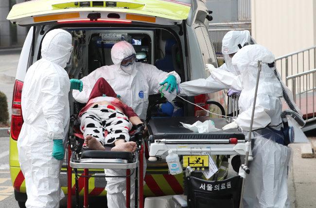 3월 11일 서울 중랑구 서울의료원에서 의료진이 코로나19 확진자를 응급실로 이송하고 있다. [뉴스1]