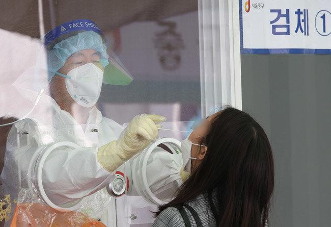 4월 15일 서울 중구 서울역 광장에 마련된 중구 임시선별진료소에서 한 시민이 코로나19 검사를 위해 검체를 채취고 있다. [뉴스1]