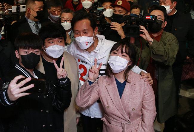3월 31일 오세훈 당시 국민의힘 서울시장 후보가 서울 동작구 총신대입구역 앞에서 청년들과 기념촬영을 하고 있다. [뉴스1]