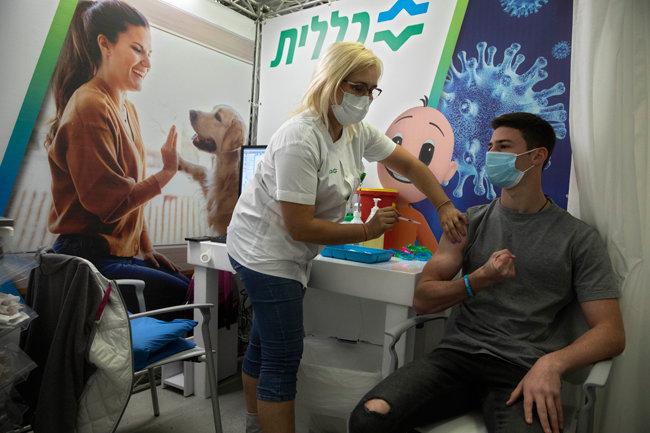 한 이스라엘 청소년이 텔아비브 접종센터에서 화이자가 개발한 코로나19 백신을 접종하고 있다. [AP뉴시스]