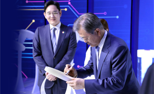 문재인 대통령(오른쪽)이 2019년 4월 30일 경기 화성 삼성전자 화성사업장에서 열린 '시스템반도체 비전 선포식'에서 이재용 삼성전자 부회장이 지켜보는 가운데 EUV공정 7나노로 출하된 웨이퍼 칩에 서명하고 있다. [청와대사진기자단]