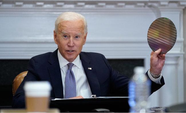 조 바이든 미국 대통령이 4월 12일(현지 시간) 백악관에서 반도체·자동차·IT 기업 경영진을 초청해 화상회의를 진행하는 도중 손에 반도체 핵심 소재인 웨이퍼를 들고 발언하고 있다. [AP=뉴시스]
