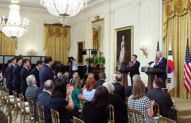 """문재인 대통령과 조 바이든 미국 대통령이 5월 21일(현지 시간) 백악관 이스트룸에서 공동 기자회견을 하는 도중 한국 기업인들에게 박수를 치고 있다. 바이든 대통령은 이들에게 일어나줄 것을 요청한 뒤 미국 투자에 대해 """"감사하다""""는 말을 세 번 반복했다. 오른쪽부터 최태원 SK그룹 회장, 김기남 삼성전자 부회장, 김종현 LG에너지솔루션 사장, 존 림 삼성바이오로직스 사장, 안재용 SK바이오사이언스 사장, 공영운 현대자동차 사장. [뉴시스]"""
