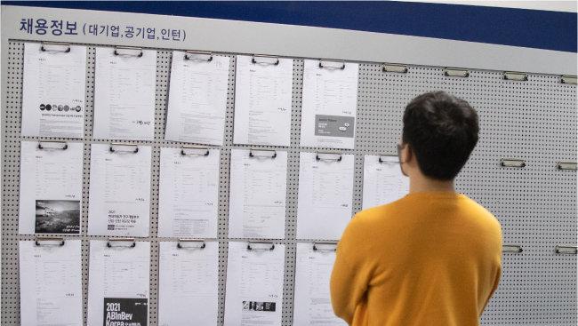 4월 12일 서울의 한 대학 취업 정보 게시판 앞에서 학생이 채용 공고문을 확인하고 있다. [뉴스1]