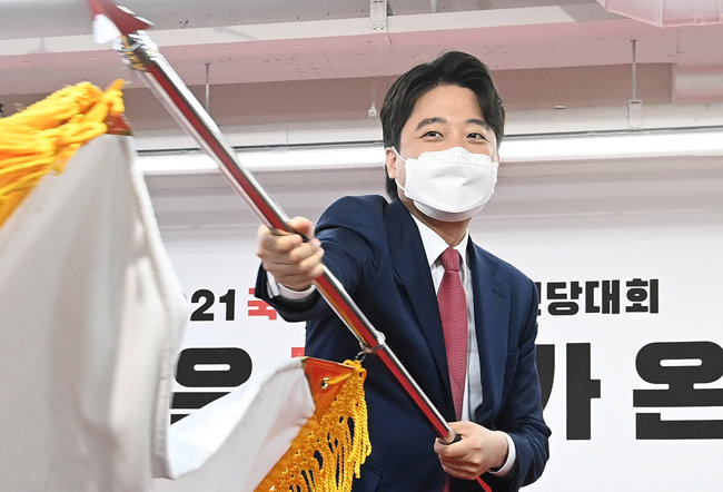 이준석 신임 국민의힘 당대표가 6월 11일 서울 여의도 국민의힘 당사에서 열린 전당대회에서 당기를 흔들고 있다. [뉴시스]