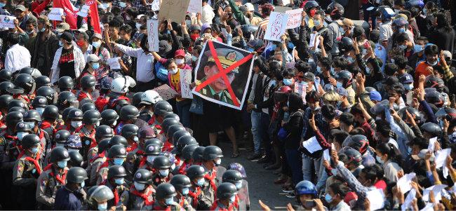 2월 8일 미얀마 네피도 거리에서 시민들과 군인이 대치하고 있다. 시민들은 민아웅 흘라잉 군 총사령관 모습 위에 크게 'X'자를 쳐놓은 사진을 들고 있다. [AP 뉴시스]
