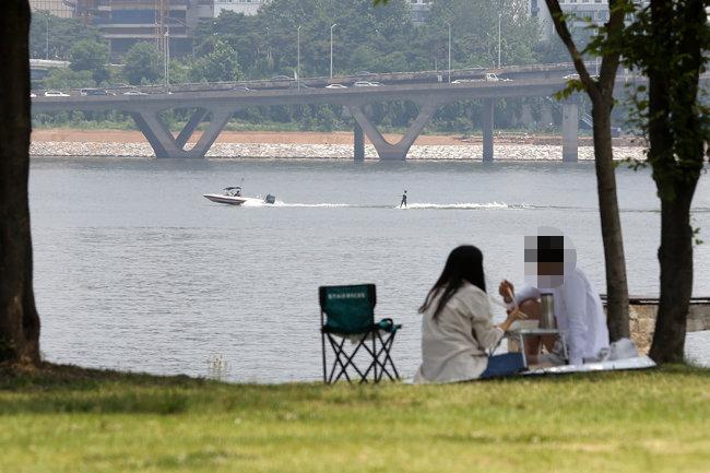 6월 6일 서울 여의도 한강공원을 찾은 시민들이 나무그늘 아래 돗자리를 펴놓고 시간을 보내고 있다. [뉴스1]