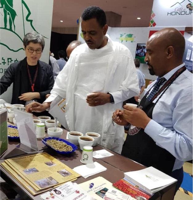 윤오순 박사(왼쪽)가 2019년 일본에서 열린 스페셜티 커피 엑스포에서 주일본 에티오피아 대사(가운데)에게 에티오피아 커피에 대해 설명하고 있다. [윤오순 제공]