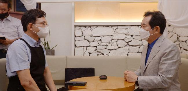 광주에서 카페를 운영하는 자영업자 배훈천 씨(왼쪽)가 7월 2일 자신의 카페에서 정세균 전 국무총리와 대화를 나누고 있다. 배씨는 한 집회에 참석해 문재인 정부의 경제정책을 비판하는 내용의 연설을 했다가 고초를 겪었다. [뉴스1]