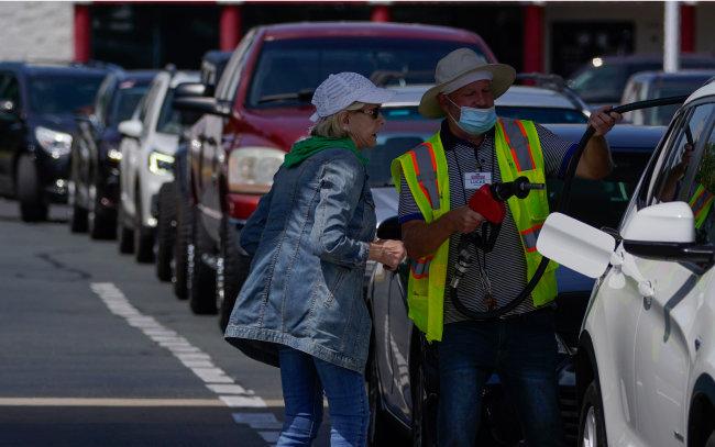 6월 11일 미국 노스캐롤라이나주 한 주유소에서 직원이 휘발유를 채우려는 고객을 돕고 있다. 그 뒤로 긴 차량 행렬이 이어져 있다. 미국 최대 송유관 운영업체 콜로니얼 파이프라인이 랜섬웨어 공격을 받아 운영이 전면 중단된 후 휘발유 가격이 6년 반 만에 최고가를 기록했다. [AP 뉴시스]