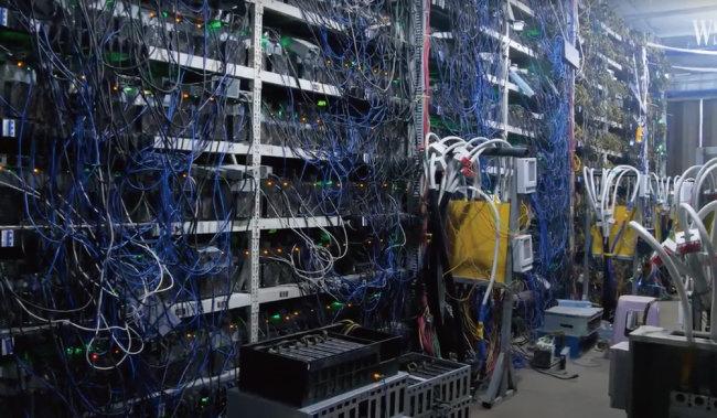 중국 쓰촨성에 있는 한 비트코인 채굴장 내부. 수백여 개의 그래픽카드에 연결된 전선이 얽혀 있다. [월스트리트저널 유튜브채널 캡처]