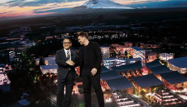 도요다 아키오 도요타 사장(왼쪽)과 비야케 잉겔스 건축가가 지난해 1월 6일 미국 라스베이거스에서 열린 'CES 2020'에서 '우븐시티' 계획을 발표하며 악수하고 있다. [AP=뉴시스]