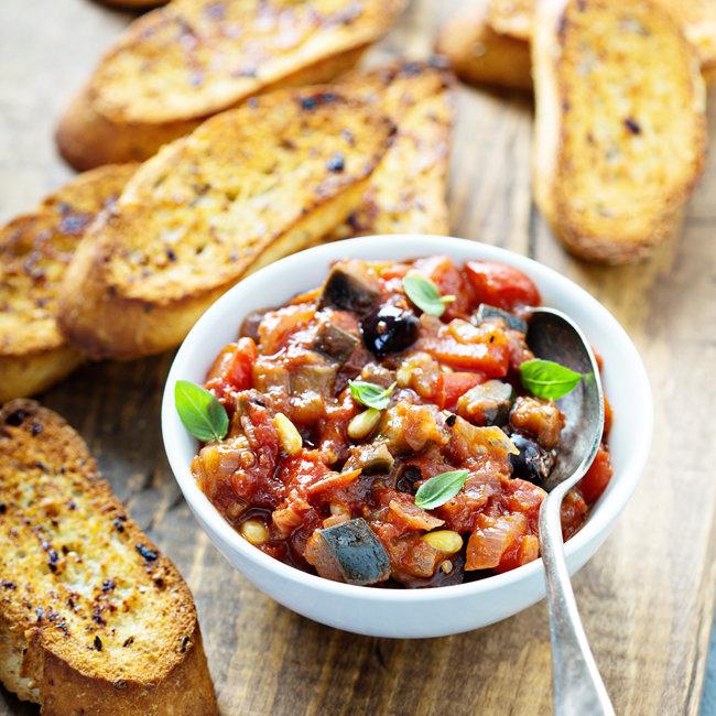 가지를 비롯한 여러 채소를 깍두기 모양으로 썬 뒤 뭉근하게 끓여 만든 카포나타. 바삭한 빵에 소복하게 올려 먹으면 그 맛이 일품이다. [GettyImage]