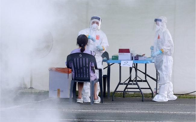 8월 5일 폭염이 발생한 대구시의 한 코로나19 임시선별검사소 풍경. 열기를 식히고자 살수차가 물을 뿌리는 가운데 의료진이 코로나19 진단검사를 실시하고 있다. [뉴스1]