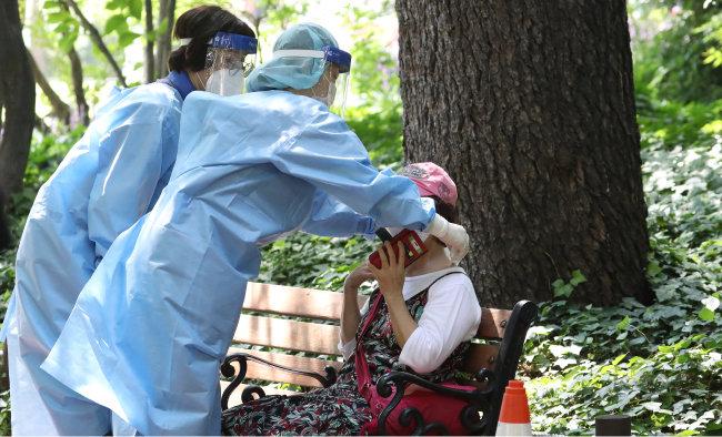 폭염이 계속된 8월 5일 대구시 한 코로나19 임시선별검사소에서 진단검사를 기다리던 60대 여성이 어지러움을 호소하며 주저앉자 근처에 있던 의료진이 달려와 얼음 스카프를 채워주고 있다. [뉴스1]