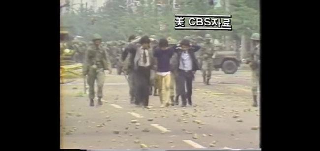1980년 5월 미국 CBS 뉴스에 보도된 광주항쟁 당시 모습. 젊은 남성 여러 명이 손을 머리 뒤로 깍지 낀 채 강제 연행되는 광경은 유영길 감독이 촬영한 것이다. [한국영상기자협회 제공]