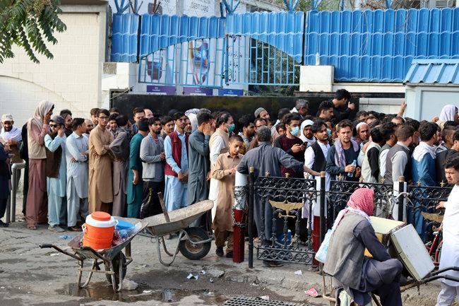 8월 30일(현지 시간) 아프가니스탄 수도 카불의 은행 앞에 현금을 찾으려는 시민들이 길게 줄을 서 있다. 탈레반이 아프간을 장악한 후 현금 인출 수요가 폭증하자 탈레반은 시민들의 인출 금액을 한 주에 200달러로 제한했다. [AP 뉴시스]