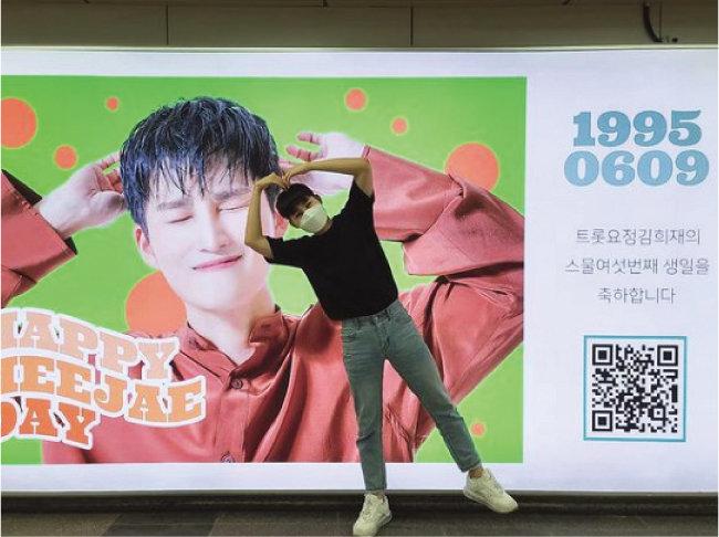 지난해 김희재가 자신의 스물여섯 번째 생일을 축하하기 위해 팬들이 선물한 지하철 광고 패널 앞에서 행복감을 감추지 못하고 있다. [김희재 인스타그램]