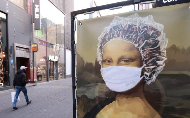 2월 8일 서울 중구 명동 거리에 한 시민이 지나가고 있다. 거리에 세워진 미용실 광고판에는 마스크와 비닐캡을 쓴 모나리자 그림이 그려져 있다. [동아일보 송은석 기자]