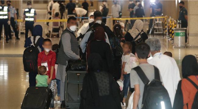 8월 26일 한국 정부에 협력한 아프간 현지 조력자 가족이 인천국제공항에 도착해 입국장을 빠져나가고 있다. [뉴시스]