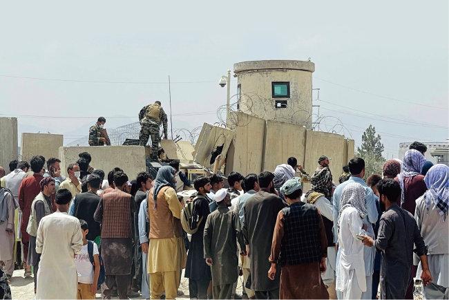 8월 16일(현지 시간) 아프가니스탄 탈출에 나선 시민들이 카불 국제공항으로 들어가기 위해 담을 넘고 있다. [뉴스1]